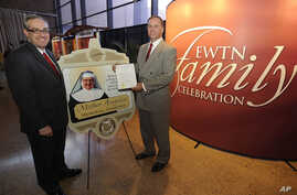FILE - EWTN Global Catholic Network President and CEO Michael P. Warsaw, left, reacts with pleasure as Canton, Ohio Mayor William Healy, honors EWTN Foundress Mother Angelica.