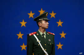 FILE - A Chinese policeman stands in front of the European Union flag outside the office of the European Union delegation to China in Beijing, Oct. 28, 2011. The chamber said the EU is unlikely to lift trade barriers later this year because of growin
