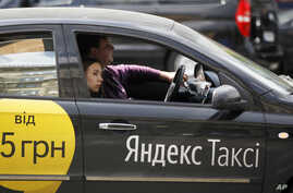 FILE - A woman rides in a Yandex taxi in Kiev, Ukraine, May 16, 2017.