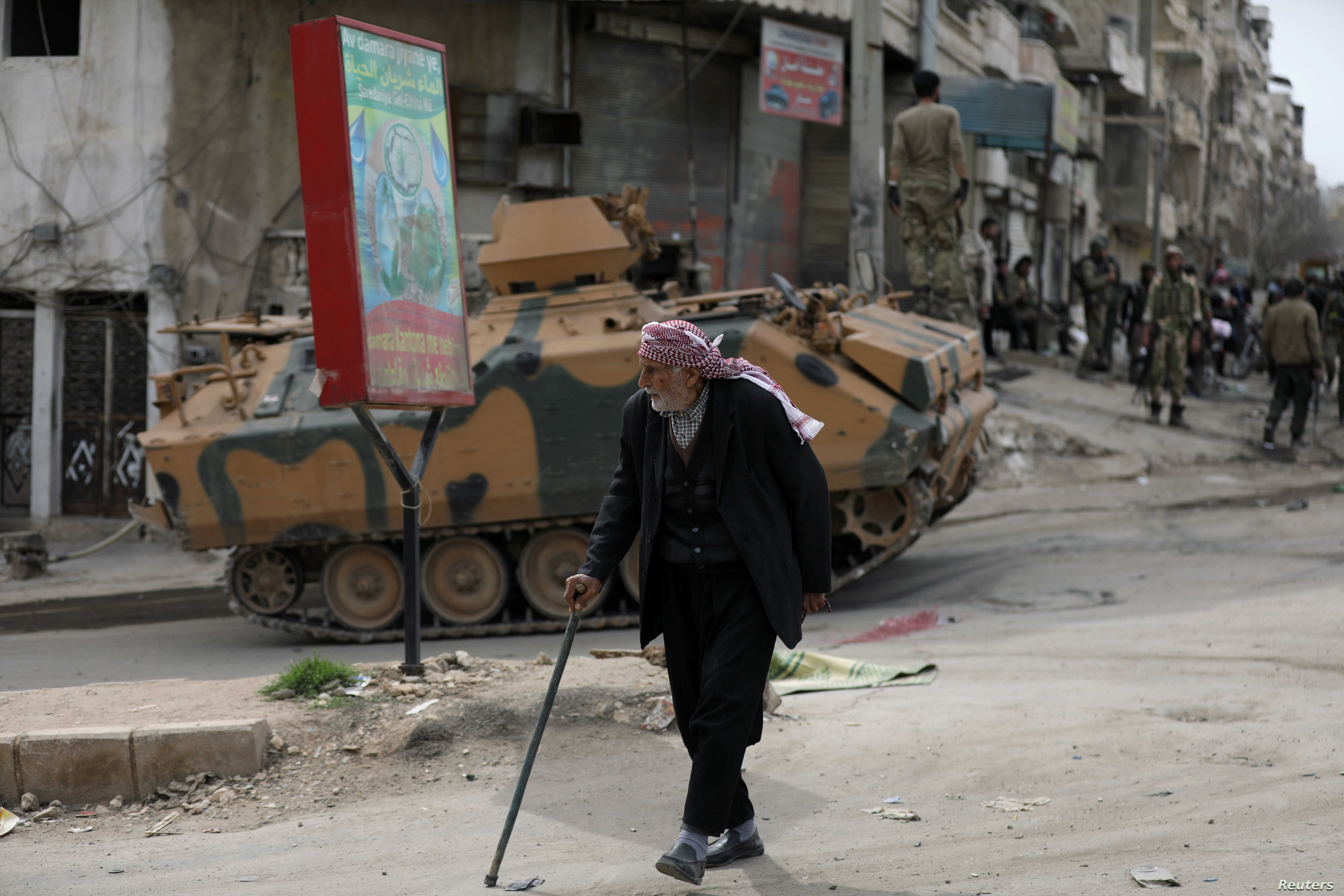 A Kurdish elderly man walks with a cane in Afrin, Syria, March 19, 2018.