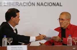 Frank Pearl, left, head of Colombia's peace negotiation team, hands documents to Antonio Garcia, chief negotiator of the National Liberation Army, or ELN, during a signing agreement to start peace talks, in Caracas, Venezuela, March 30, 2016.