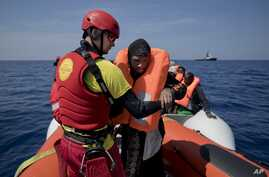 FILE - Proactiva Open Arms lifeguard Ivan Martinez, from Spain, rescues migrants from a rubber boat sailing out of control, in the Mediterranean sea, about 56 miles north of Sabratha, Libya, April 6, 2017.