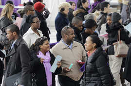 FILE - A crowd of job seekers attends a health care job fair  in New York, March 14, 2013.