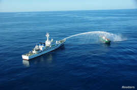 An aerial view shows a Japan Coast Guard patrol vessel spraying water at a fishing boat from North Korea, in an area called the Yamato Shallows about 400 kilometers off the western coast of Japan, in this handout photo taken in September 2017.
