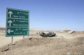 The wreckage of a car belonging to Islamic State militants lies along a road after it was targeted by a U.S. air strike at the entrance to the Mosul Dam, northern Iraq, Aug. 21, 2014.