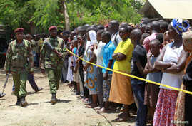 Kenyan police men walk past members of the public standing behind the cordoned off area outside the church where gunmen attacked worshippers attending a church service at the Coast coastal town of Mombasa, Kenya, March 23, 2014.