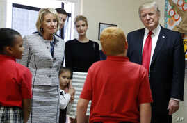 President Donald Trump, Education Secretary Betsy DeVos, his daughter Ivanka and Janayah Chatelier, 10 (L) listen to Landon Fritz, 10, during a tour of Saint Andrew Catholic School, March 3, 2017, in Orlando, Fla.