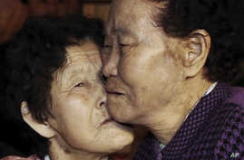 South Korean Lee Chun Hwa, right, gets a kiss from her North Korean sister Lee Chun Son before returning home after a separated family reunion meeting at the Diamond Mountain resort in North Korea, Feb. 22, 2014.