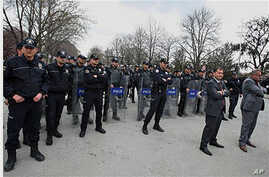 Riot police stand at the entrance of parliament in Ankara, as dozens of Turkish women stage a demonstration to protest the rape and killings of children and women in Turkey,  April 14, 2011