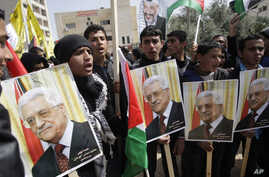 Palestinians shout slogans to support Palestinian President Mahmoud Abbas ahead of his meeting with U.S. President Barack Obama Monday, Tubas, West Bank, March 16, 2014.