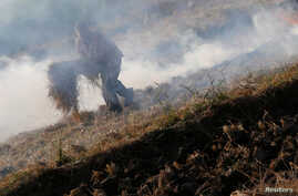 """FILE - A farmer burns rice straw at his field in Qalyub, causing a """"black cloud"""" of smoke that spreads across the Nile valley, near the agricultural road which leads to the capital city of Cairo, Egypt, Oct. 26, 2016."""