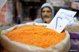 An Egyptian man buys consumer goods as yellow lentils, at a vegetable market in Cairo, Egypt January 10, 2017.