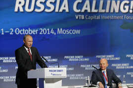 """Russia's President Vladimir Putin (L) speaks during the VTB Capital """"Russia Calling!"""" Investment Forum in Moscow October 2, 2014."""