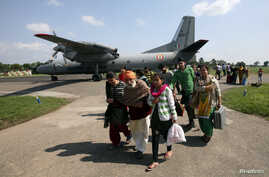 Evacuees from Srinagar city walk past an Indian Air Force AN-32 aircraft in Jammu, Sept. 9, 2014.