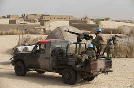 FILE - UN peacekeepers from Burkina Faso stand guard during a patrol through a neighborhood on the outskirts of Timbuktu, Mali. Hundreds of Malians are gathering in the northern desert town of Timbuktu, from Monday, March 31, 2014,