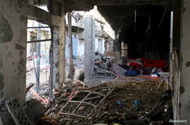 A man rests inside a building destroyed during recent fighting in Yemen's southwestern city of Taiz, March 14, 2016.