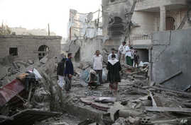 FILE - People inspect the damage of houses destroyed by Saudi-led airstrikes in Sanaa, Yemen, Jun. 9, 2017.