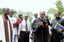 Pastor Martin Ssempa (pointing) and Julius Oyet arrive at the Ugandan Parliament to discuss the Anti-Homosexuality Bill, April 6, 2011