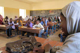 FILE - Schoolchildren listen to a teacher during class in Douentza, Mali. In schools funded by radical Islamists, girls must wear veils and are being seated separately in the back or coming at different times altogether.