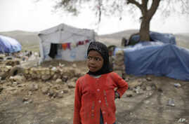 A displaced girl stands outside her family's hut at a camp for internally displaced people in the outskirts of Sanaa, Yemen, May 27, 2016. Yemen's war has killed at least 6,200 civilians and injured tens of thousands of Yemenis, and 2.4 million peopl