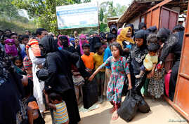 FILE - Rohingya refugees collect aid supplies including food and medicine, sent from Malaysia, at Kutupalang Unregistered Refugee Camp in Cox's Bazar, Bangladesh, Feb. 15, 2017.