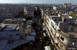 FILE - A general view taken with a drone shows part of the rebel-held Idlib city, Syria, June 8, 2017.