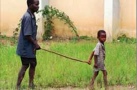 FILE - A child leads a man affected by river blindness in Gbarnga, Liberia, Sept. 4, 1995.