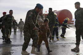 An Afghan National Army officer escorts a slightly injured boy from the site of a suicide attack on the outskirts of Mazar-e-Sharif, Afghanistan, Feb. 8, 2016.
