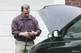 FILE - James Everett Dutschke works on his minivan in his driveway in Tupelo, Mississippi, April 2013.