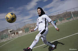 FILE - A female soccer player controls a ball during a training session at the Golab Trust Sport Complex in Kabul, Afghanistan.