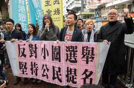 This picture taken March 26, 2017 shows activist Raphael Wong of the League of Social Democrats Raphael Wong (3rd R in rear) and Umbrella Movement protester Shiu Ka-chun (R) joining fellow protesters as they prepare to march in protest to the venue o