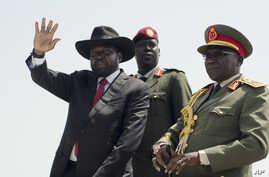 South Sudan's President Salva Kiir, left, accompanied by army chief of staff Paul Malong, right, waves during an independence day ceremony in the capital Juba, South Sudan.