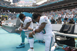 Miami Dolphins wide receiver Kenny Stills (10) and Miami Dolphins wide receiver Albert Wilson (15) kneel during the national anthem before an NFL football game against the Tennessee Titans, Sunday, Sept. 9, 2018, in Miami Gardens, Florida.