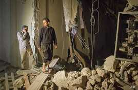 In this photo taken on a government organized tour, officials inspect damage at a building following an airstrike in Tripoli, Libya, early Saturday, April 30, 2011