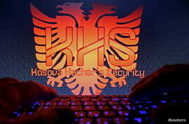 """A man types in front of the logo of the """"Kosova Hackers Security"""" in this photo illustration taken in Sarajevo, Bosnia and Herzegovina, Oct. 16, 2015. Ardit Ferizi, arrested in Malaysia on charges of stealing information on Americans, is thought to b"""