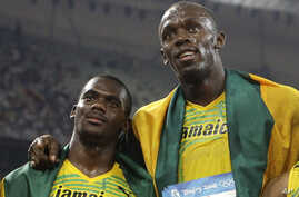 FILE - In this Friday, Aug. 22, 2008 file photo members of Jamaica's gold medal winning relay team Nesta Carter and Usain Bolt, right, celebrate after the men's 4x100-meter relay final during the athletics competitions in the National Stadium at the