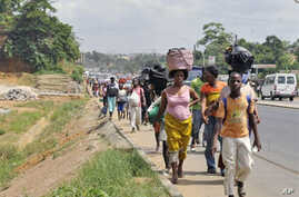 Residents of the popular district of Abobo, a suburb of Abidjan, flee the quarter carrying their luggage on their heads, February 25, 2011