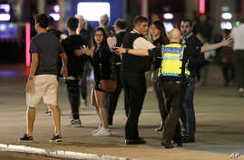 A police officer clears people away from the area near London Bridge after an incident in central London, late Saturday, June 3, 2017.