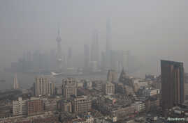 FILE - The financial district of Pudong is seen on a hazy day in Shanghai, March 18, 2014.