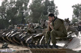 Israeli soldiers with armored vehicles gather in a staging ground near the border with Gaza Strip, southern Israel, Friday, Nov. 16, 2012.