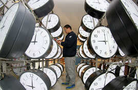 A technician checks on the synchronization system at a workshop of a clock manufacturer in Yantai, Shandong province, China, Jan. 21, 2019.