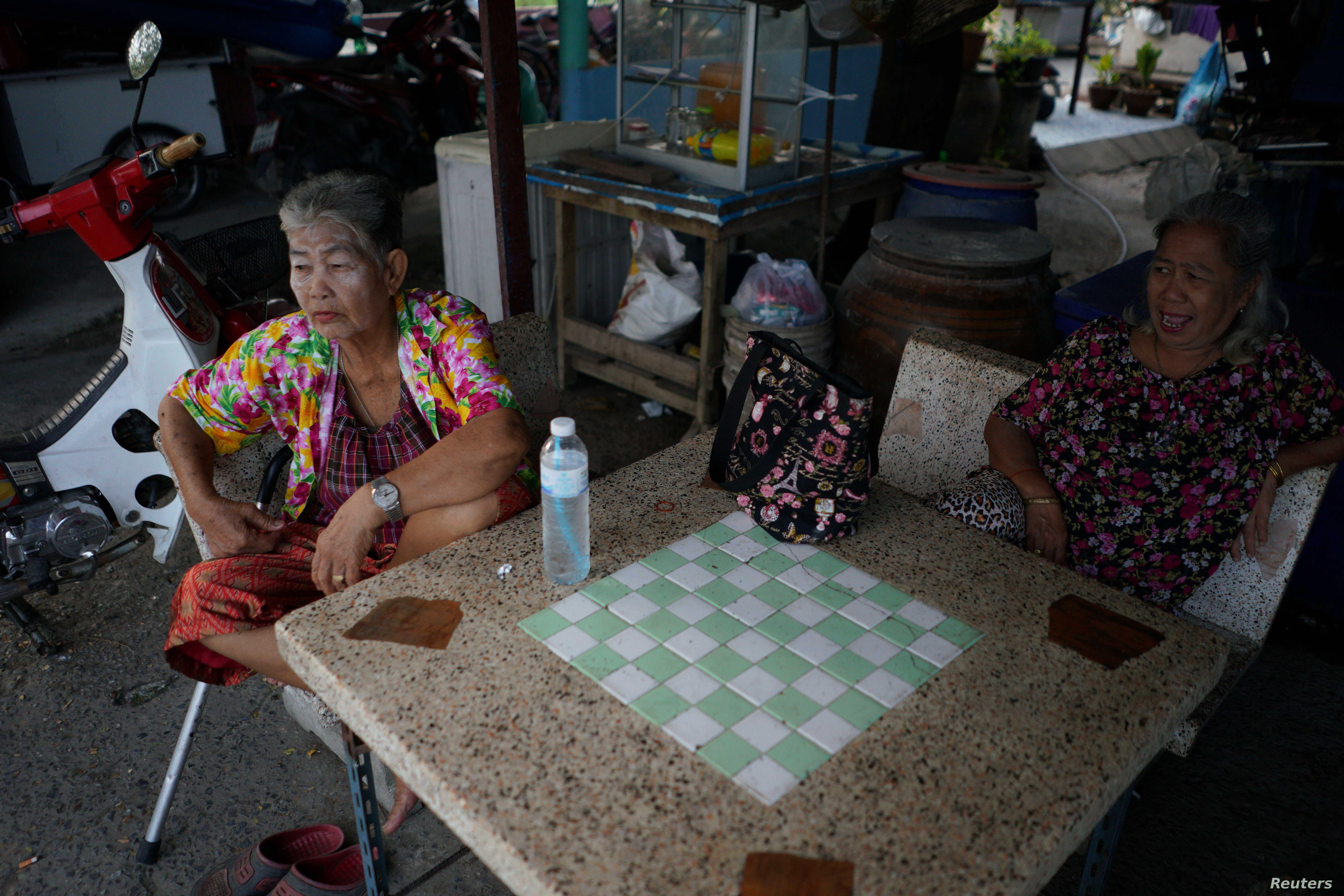 Somjit Teeraroj (L), 77, and Poonsri Seangnual (R), 63, who study at the School for the Elderly in Chiang Rak Noi subdistrict, spend time with each other at a shop in Ayutthaya, Thailand, April 26, 2018.