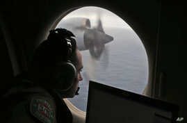 FILE - In this March 22, 2014, photo, a flight officer aboard a Royal Australian Air Force plane, searches for signs of missing Malaysia Airlines Flight MH370 in the southern Indian Ocean off Australia.