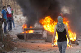 A Palestinian demonstrator holds rocks during clashes with Israeli security forces, at Hizme checkpoint near the West Bank city of Ramallah, Sept. 30, 2015.