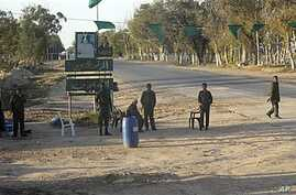 In this image taken during a trip organized by Libyan authorities, Libyan soldiers control a checkpoint near the city of Misrata, April 9, 2011