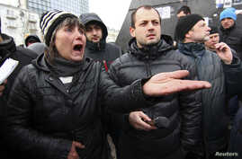 Pro-Russian supporters take part in a rally outside the regional administration in Donetsk.  The US and the European Union imposed sanctions including asset freezes and travel bans on officials from Russia and Ukraine after Crimea applied to join Rus