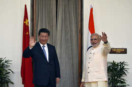 India's Prime Minister Narendra Modi, right, and China's President Xi Jinping wave to the media during a photo opportunity ahead of their meeting at Hyderabad House in New Delhi, Sept. 18, 2014.