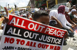 A Filipino Muslim flashes the peace sign as he holds a placard during a 'Prayer-for-Peace' rally near the Presidential Palace in Manila, Philippines, October 28, 2011.