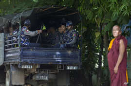 A Buddhist monk stands next a truck full of police officers during a gathering at a courthouse in support of five Buddhist monks who were forced to give up their robes in Yangon, Myanmar, also known as Burma, June 20, 2014.