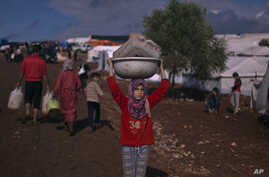A Syrian girl who fled with her family from the violence in their village, carries a plastic container over her head as she walks to fill it with water at a displaced camp, in the Syrian village of Atma, near the Turkish border with Syria, November 1